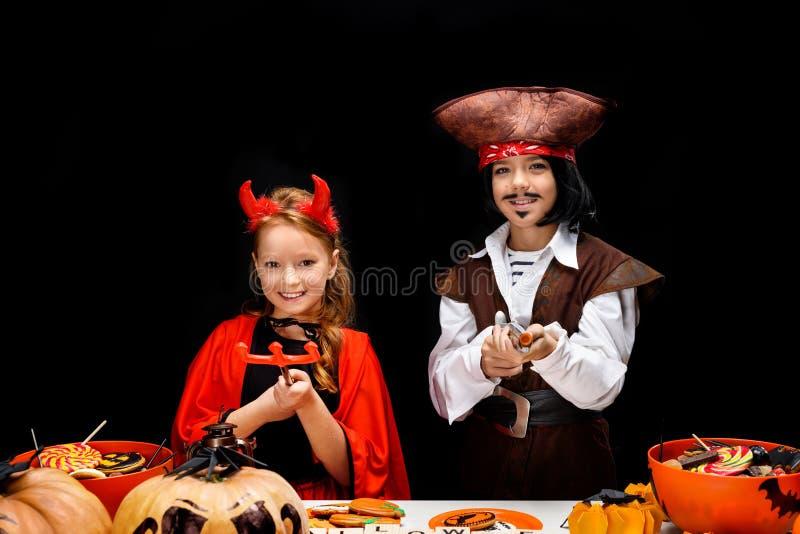 Kinder in Halloween-Kostümen des Teufels und des Piraten lizenzfreies stockbild