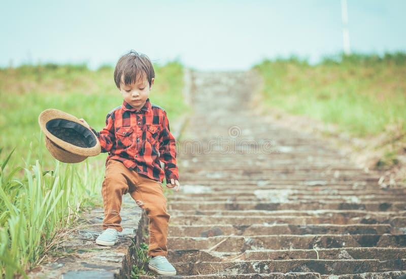 Kinder halten Hut und das Gehen auf Treppe Haben Kinder Schleim lizenzfreie stockfotografie