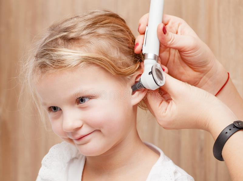 Kinder-HNOkontrolle - Untersuchungsohr Doktors von einem kleinen Mädchen mit oto lizenzfreie stockfotos