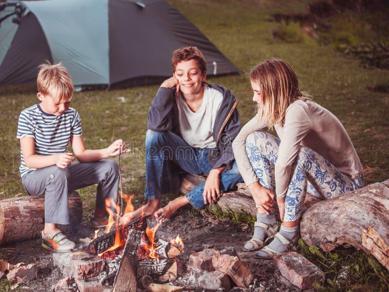 Kinder im Lager durch das Feuer lizenzfreie stockfotos