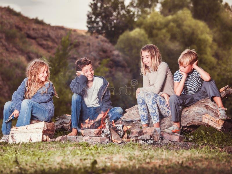 Kinder im Lager durch das Feuer lizenzfreie stockbilder
