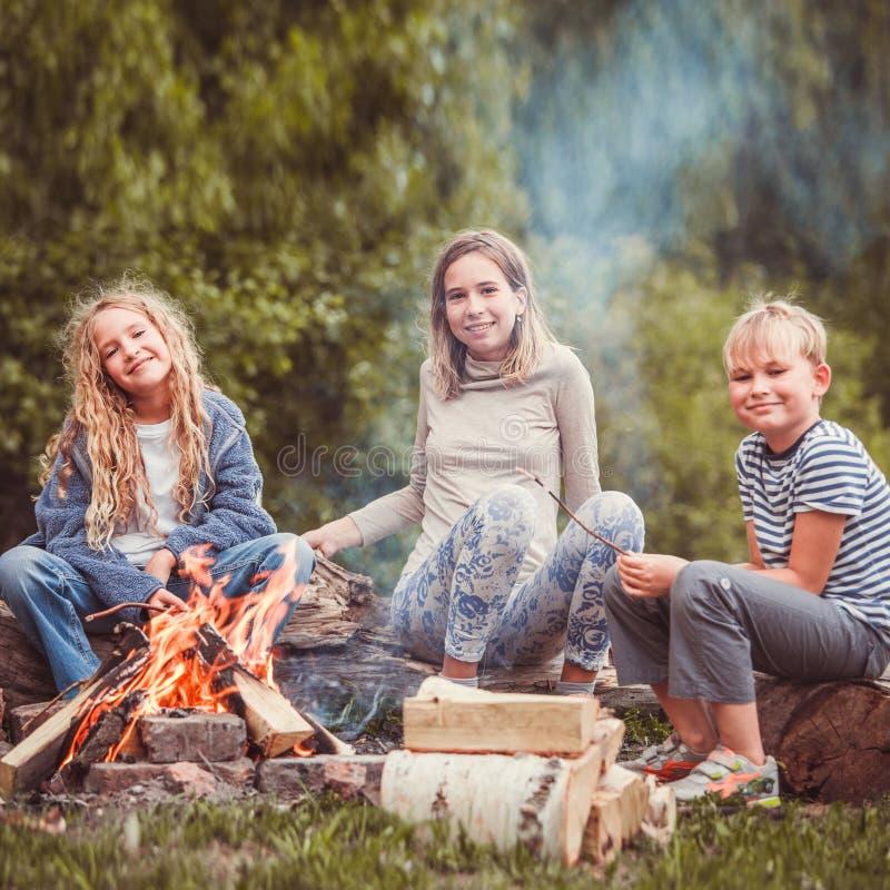 Kinder im Lager durch das Feuer lizenzfreies stockfoto