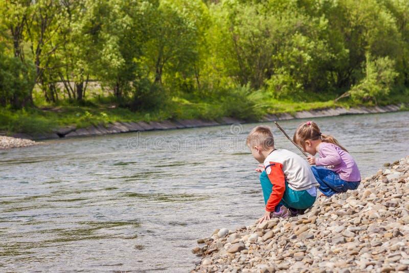 Kinder Junge und Mädchen, die nahe dem Fluss spielen lizenzfreie stockbilder