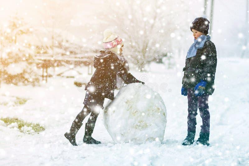 Kinder Junge und Mädchen draußen im verschneiten Winter machen einen großen Schneemann lizenzfreies stockfoto