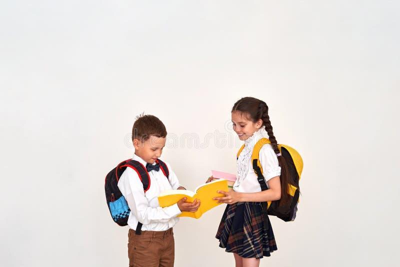 Kinder Junge und Studentinnen stehen in der Schule in Verbindung das Mädchen hilft dem Jungen, die Schulaufgabe im Lehrbuch ausei lizenzfreies stockbild