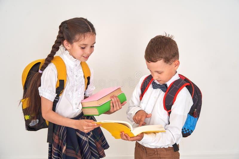 Kinder Junge und Studentinnen stehen in der Schule in Verbindung das Mädchen hilft dem Jungen, die Schulaufgabe im Lehrbuch ausei stockfoto