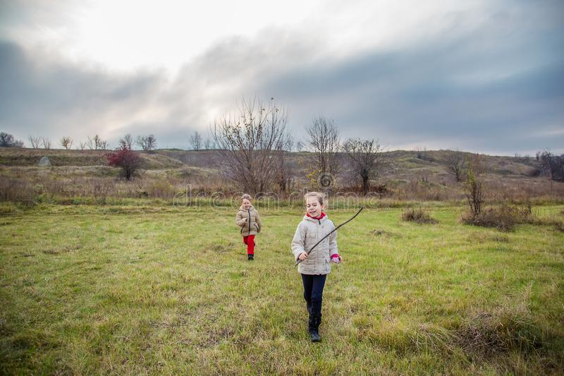 Kinder laufen gelassen in das Feld Kinderspiel auf dem Gebiet an der goldenen Stunde lizenzfreies stockfoto