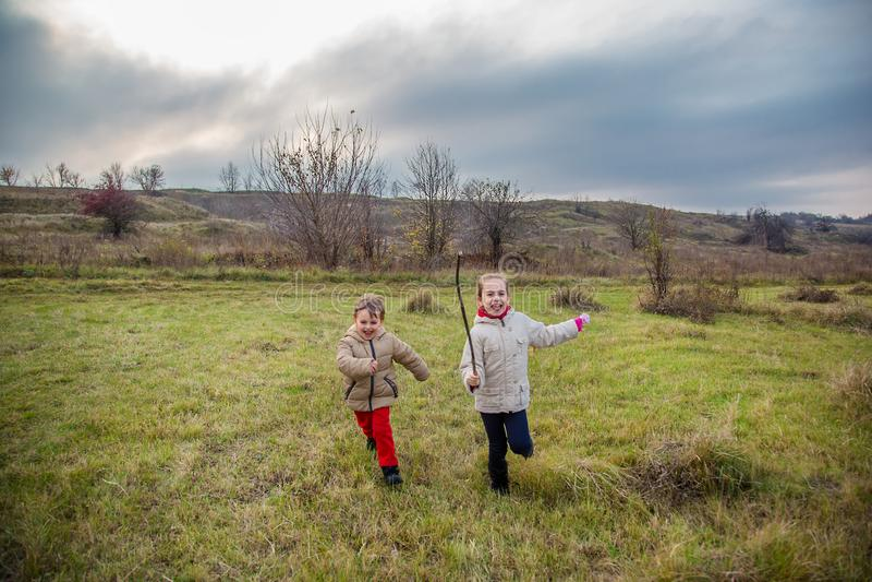 Kinder laufen gelassen in das Feld Kinderspiel auf dem Gebiet an der goldenen Stunde stockbild