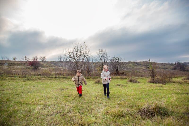 Kinder laufen gelassen in das Feld Kinderspiel auf dem Gebiet an der goldenen Stunde stockfotos