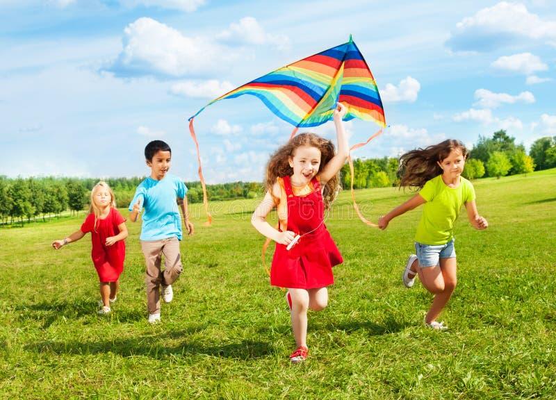 Kinder laufen gelassen mit Drachen stockfoto