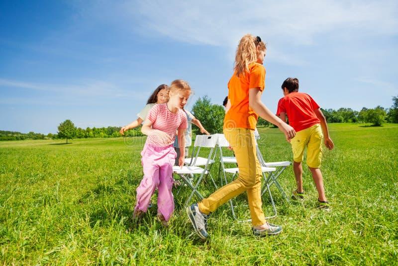 Kinder laufen um die Stühle, die draußen ein Spiel spielen lizenzfreie stockfotografie