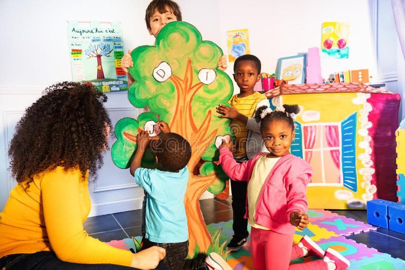 Kinder lernen Alphabet, indem sie Buchstaben auf Baum setzen lizenzfreies stockfoto