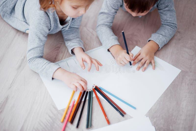 Kinder liegen auf dem Boden in den Pyjamas und zeichnen mit Bleistiften Nette Kindermalerei von den Bleistiften lizenzfreies stockfoto
