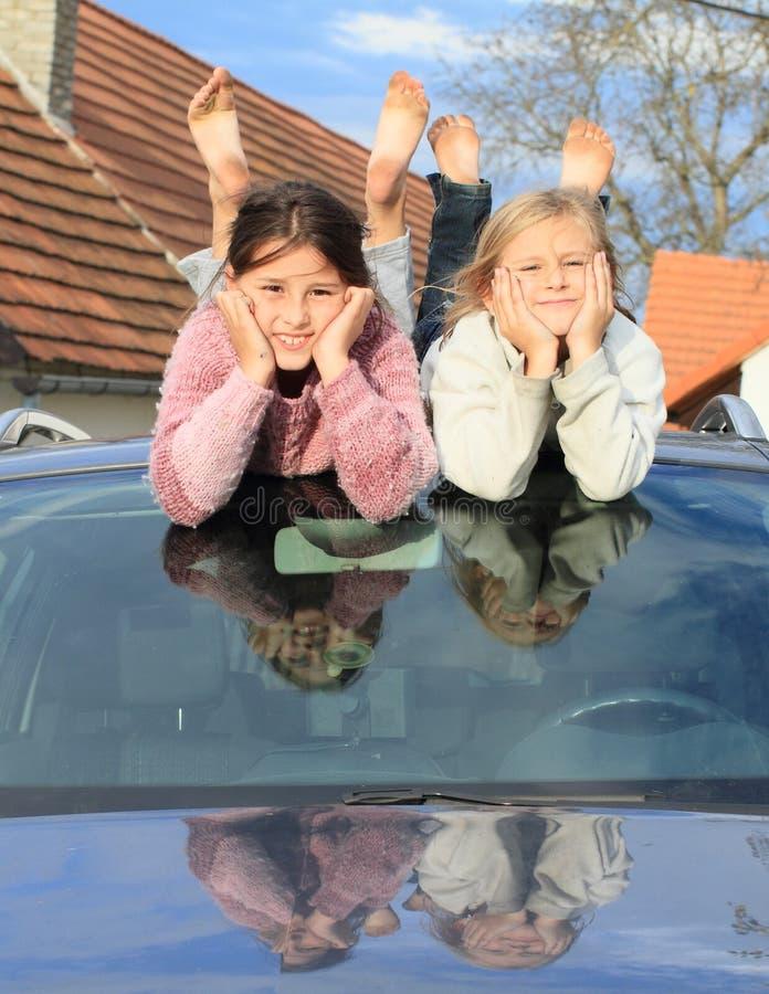 Kinder - Mädchen auf Windfang eines Autos stockbild