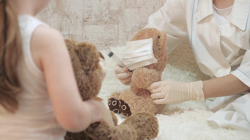 Kinder Mädchen spielen mit Spielzeugbären in medizinischen Schutzmasken Wild gibt vor, Arzt, Krankenschwester, Tierarzt zu sein, stockfoto