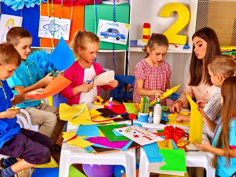 Kinder machen etwas aus farbigem Papier heraus stockbild