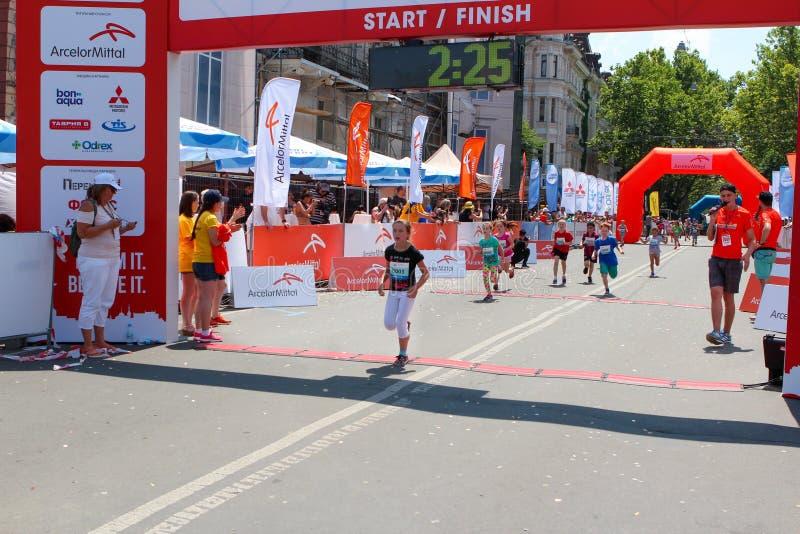Kinder Marathon, Ziellinie Marathonläufermädchen am sonnigen Sommertag lizenzfreie stockfotos