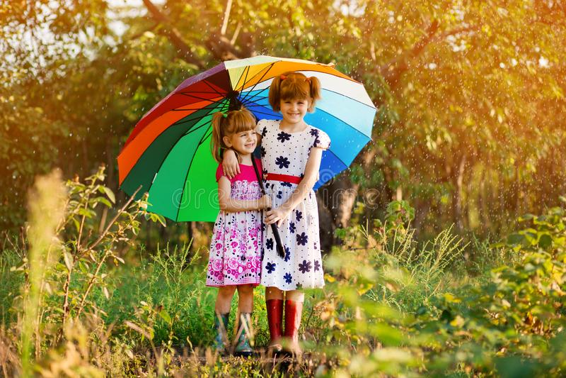Kinder mit dem bunten Regenschirm, der im Herbstduschregen spielt Wenig M?dchen spielen im Park durch regnerisches Wetter lizenzfreies stockbild