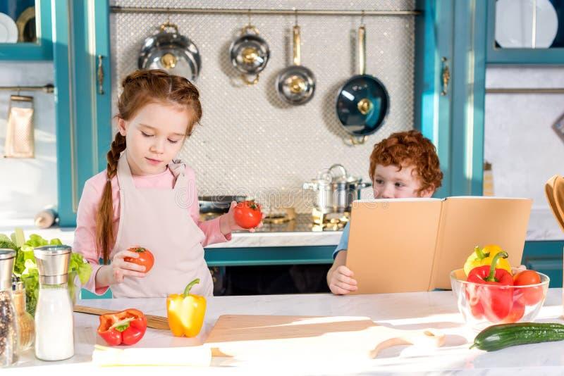 Kinder mit dem Kochbuch und Gemüse, die zusammen kochen stockbild