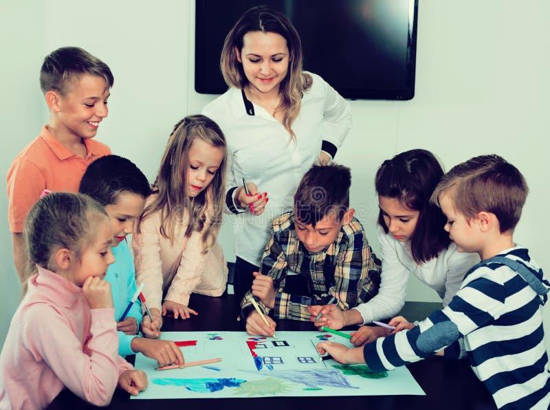Kinder mit dem Lehrer, der zusammen in Klassenzimmer zeichnet lizenzfreies stockbild