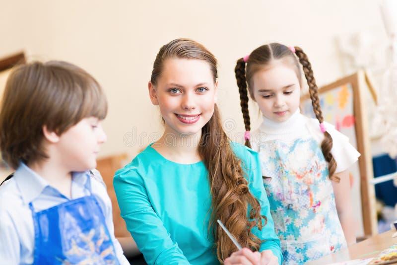 Kinder mit dem Lehrer teilgenommen an Malerei stockfoto