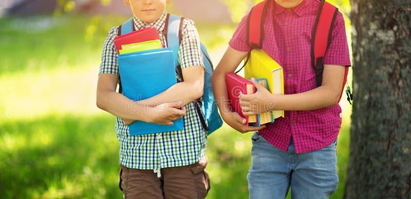 Kinder mit den Rucksäcken, die im Park nahe Schule stehen lizenzfreies stockbild
