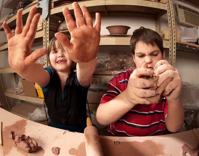 Kinder mit den unordentlichen Händen im Lehmstudio lizenzfreie stockfotos