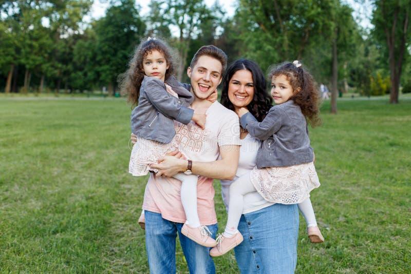 Kinder mit Eltern im Park Haming Spaß der netten Familie in der Natur Doppelkleinkindschwestern, die Eltern halten Glückliches Fa lizenzfreie stockbilder