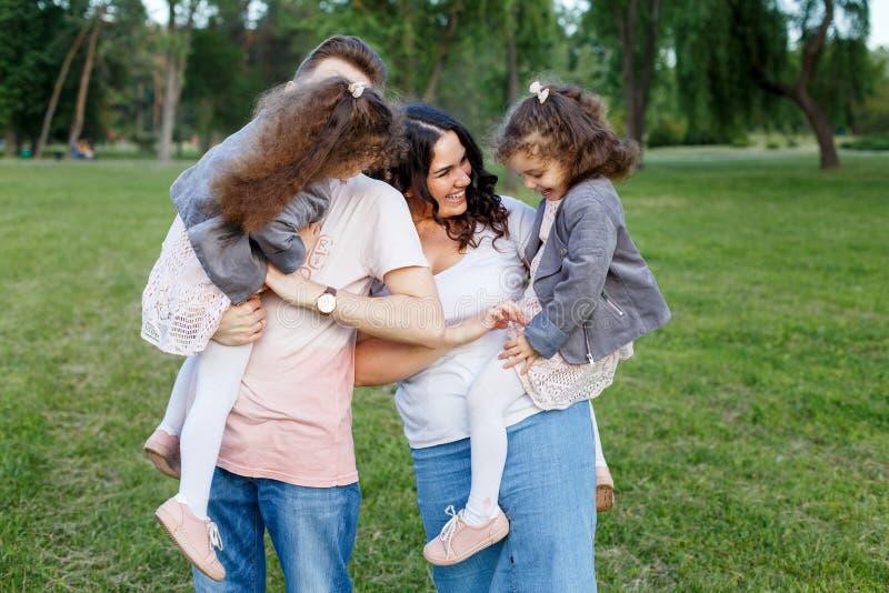 Kinder mit Eltern im Park Haming Spaß der netten Familie in der Natur Doppelkleinkindschwestern, die Eltern halten Glückliches Fa stockbilder