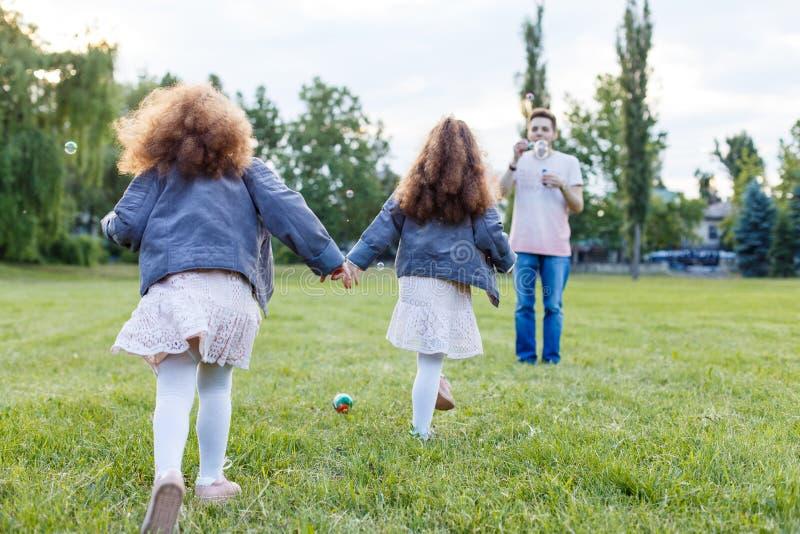 Kinder mit Eltern im Park Haming Spaß der netten Familie in der Natur Doppelkleinkindschwestern, die Eltern halten Glückliches Fa lizenzfreies stockbild