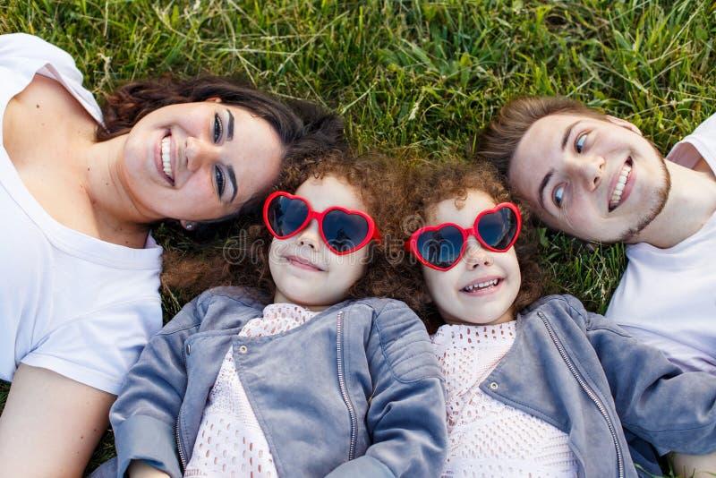 Kinder mit Eltern im Park Haming Spaß der netten Familie in der Natur Doppelkleinkindschwestern, die Eltern halten Glückliches Fa stockfoto