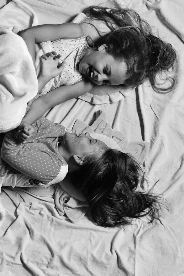 Kinder mit glücklichen Gesichtern haben Bettruhe Mädchen liegen auf dem weißen und rosa Bettlakenhintergrundkitzeln stockbilder