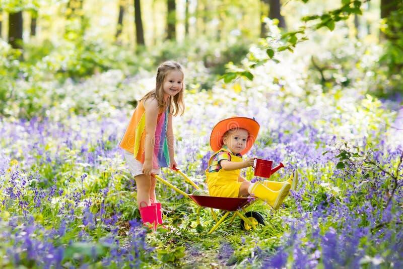 Kinder mit Glockenblumeblumen, Gartenwerkzeuge stockfotos