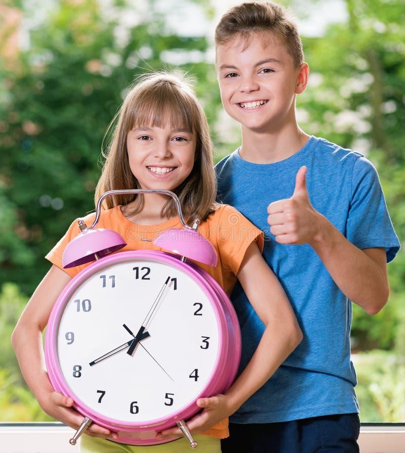 Kinder mit großer Uhr stockfotos