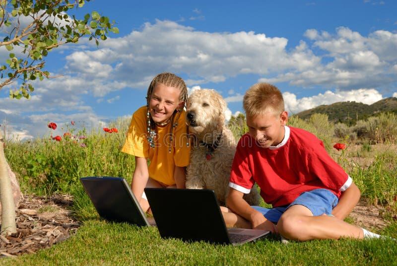 Kinder mit Hund und Laptop lizenzfreie stockfotos