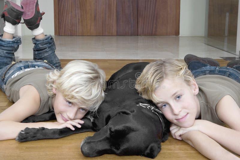 Kinder mit Hund zu Hause stockbild