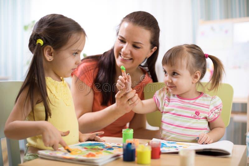 Kinder mit junger Lehrerfrauenmalerei auf Tabelle zusammen im Kindergarten lizenzfreies stockfoto