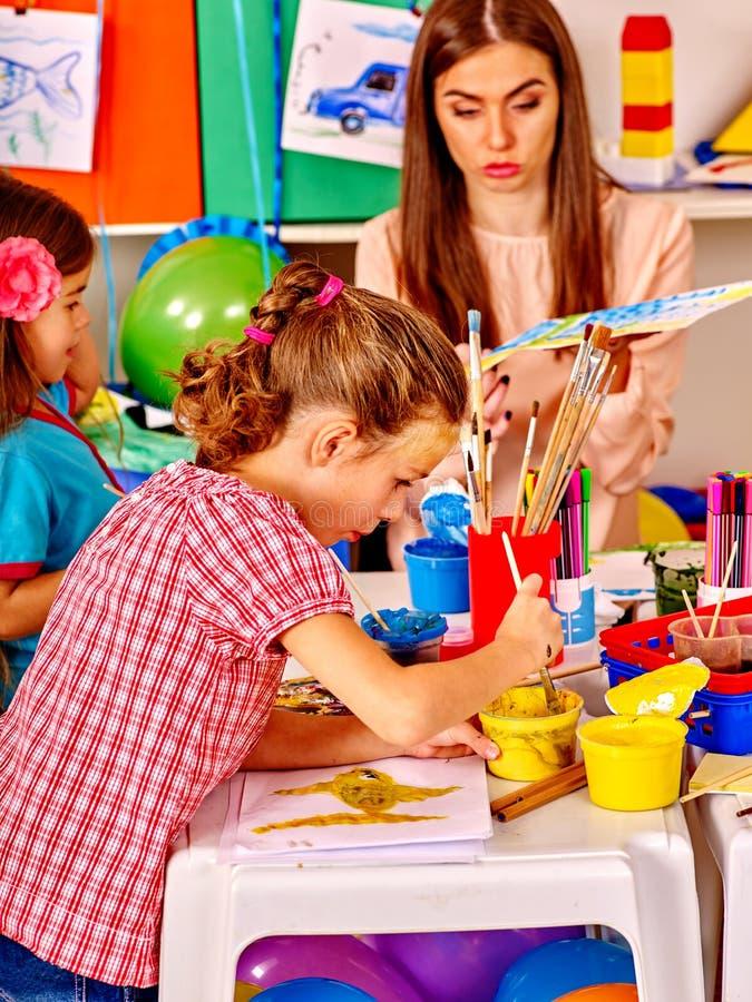 Kinder mit Lehrerfrauenmalerei auf Papier im Kindergarten lizenzfreie stockbilder