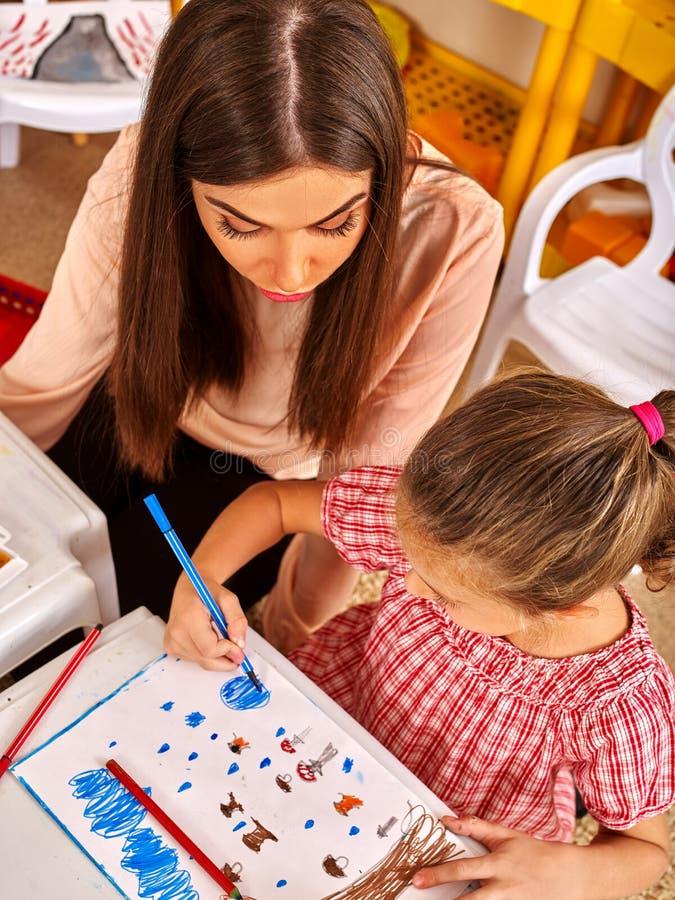 Kinder mit Lehrerfrauenmalerei auf Papier im Kindergarten stockfotografie
