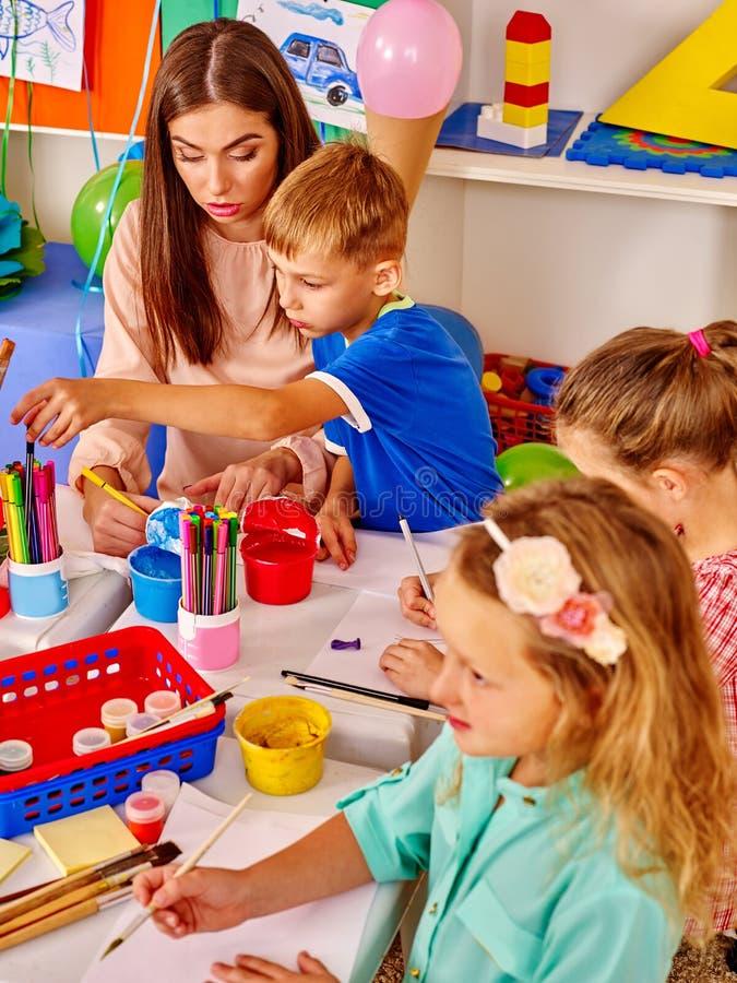 Kinder mit Lehrerfrauenmalerei auf Papier im Kindergarten stockbilder