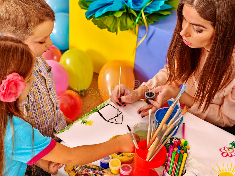 Kinder mit Lehrerfrauenmalerei auf Papier im Kindergarten stockbild