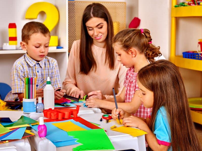 Kinder mit Lehrerfrauenmalerei auf Papier im Kindergarten lizenzfreie stockfotografie