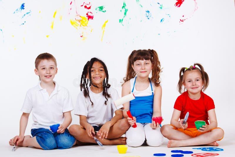 Kinder mit Malerpinseln stockfotos