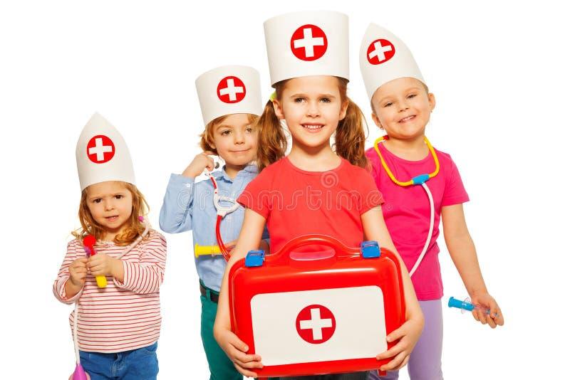 Kinder mit medizinischen Kasten- und Spielzeugdoktorinstrumenten stockbilder