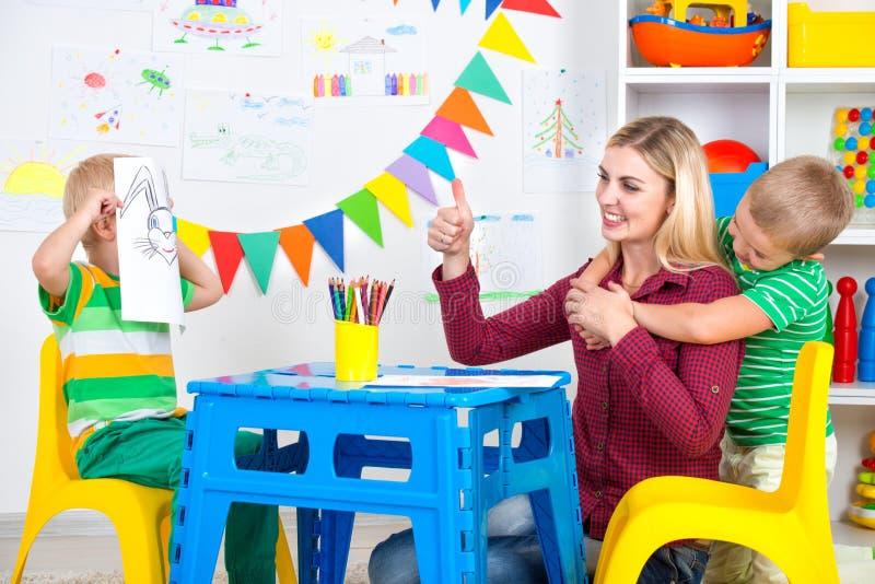 Kinder mit Mutter zeichnen Bilder im Kinderraum Haben Sie Spaß zusammen lizenzfreies stockfoto