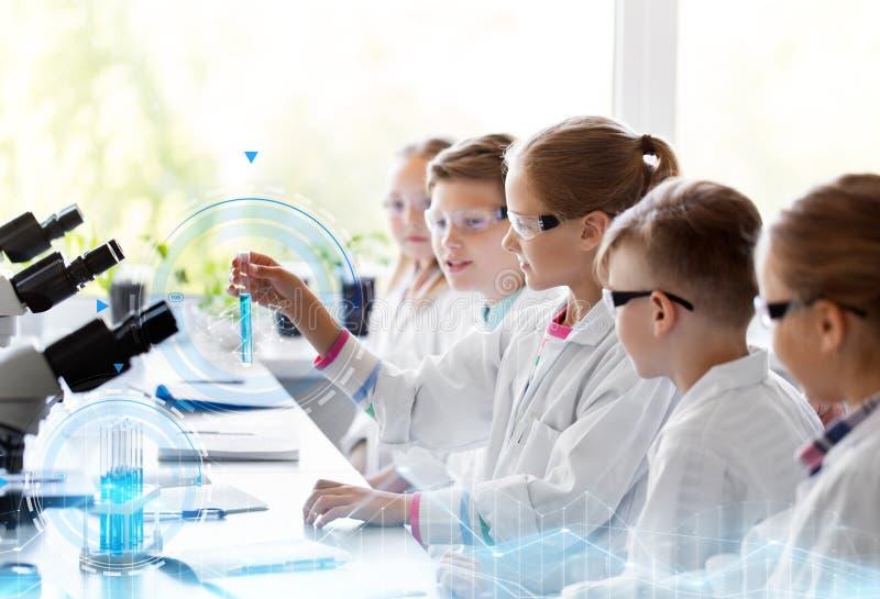 Kinder mit Reagenzgl?sern Chemie in der Schule studierend lizenzfreie stockbilder