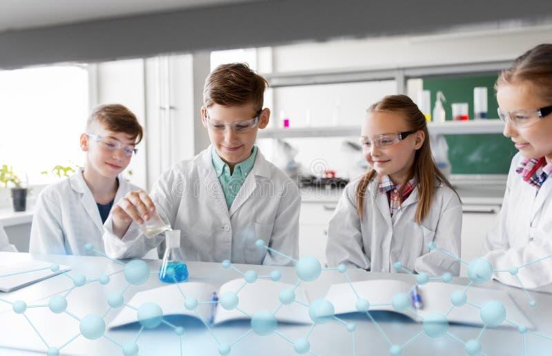 Kinder mit Reagenzglas Chemie in der Schule studierend stockfotografie