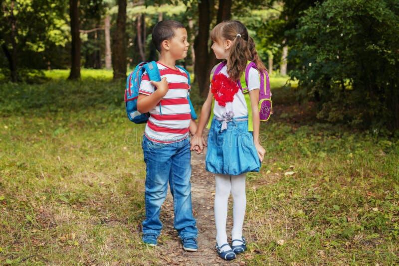 Kinder mit Rucks?cken Junge und M?dchen sind Freunde Zur?ck zu Schule Das Konzept der Ausbildung, Schule, Kindheit lizenzfreies stockfoto