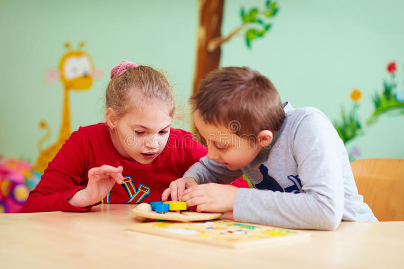 Kinder mit speziellem Bedarf entwickeln ihre feine Motilität in Kindertagesstättenrehabilitationszentrum stockfotografie