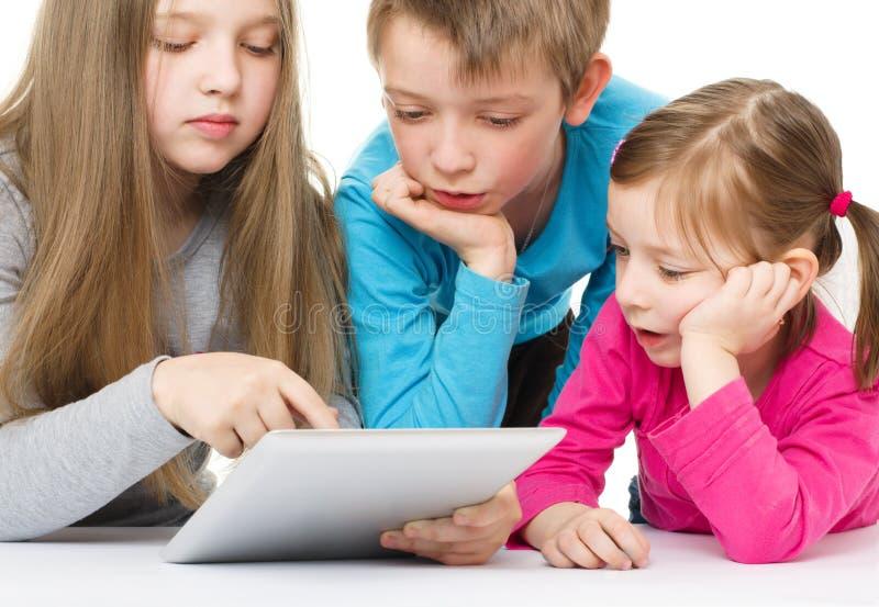 Kinder mit Tablette stockfoto